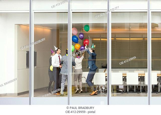 Playful business people in party hats celebrating with balloons in conference room