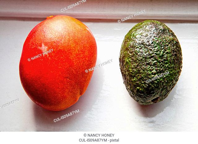 Overhead view of red and green avocados