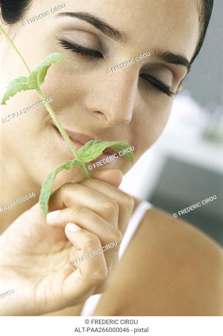 Woman holding sprig of mint under nose, eyes closed, close-up