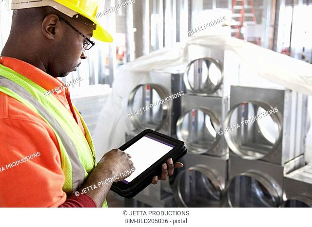 African American construction worker using digital tablet