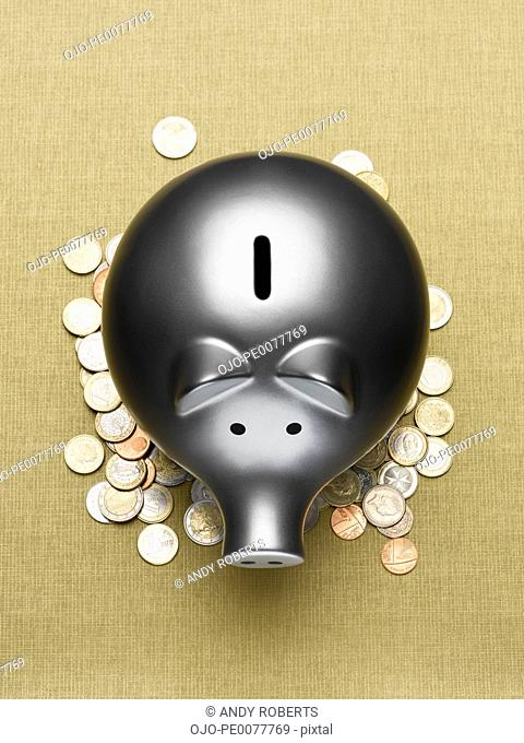 Piggy bank sitting on pile of coins