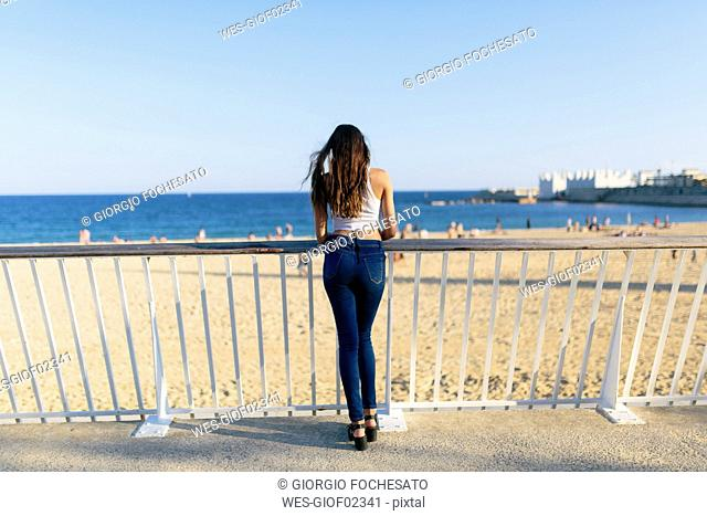 Back view of young woman standing on beach promenade looking to the sea