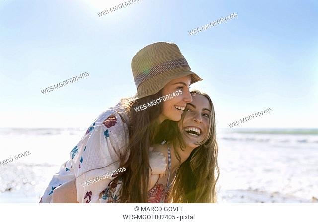 Teenage girl giving her best friend a piggyback ride on the beach