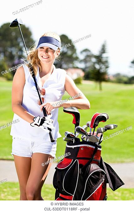 Woman with golf bag on course