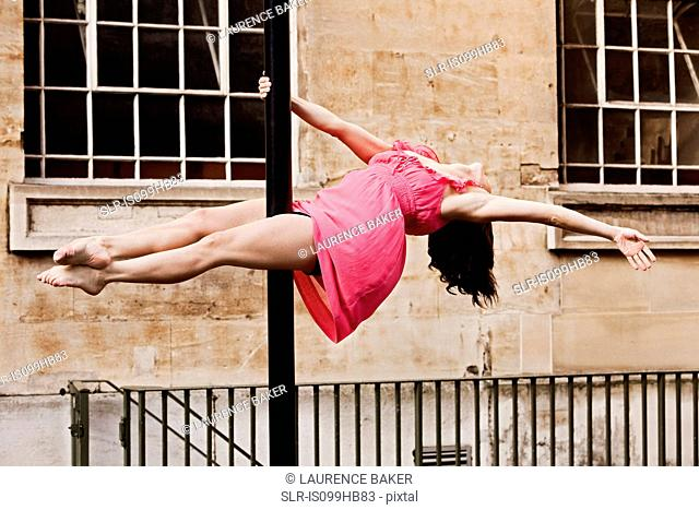 Woman in pink dress performing dance on street lamp in city