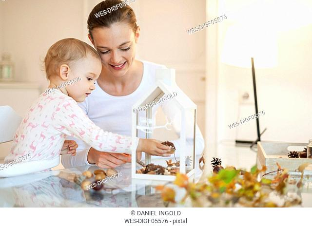 Mother and little daughter tinkering autumnal decorative house at home
