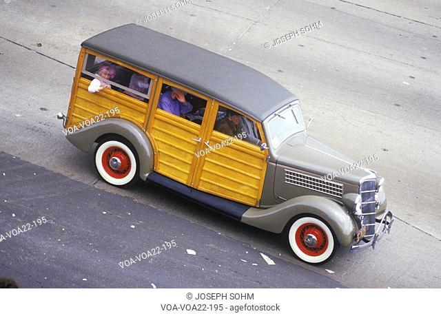 An antique Woody wagon crosses the Golden Gate Bridge in San Francisco, CA
