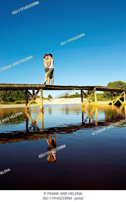 Teenage couple kissing on jetty