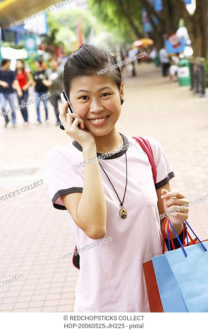 Portrait of a young woman talking on a mobile phone and carrying shopping bags