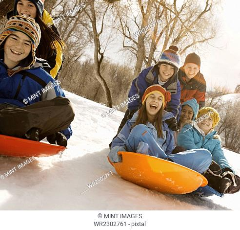 A group of children, boys and girls, riding on sledges on the snow