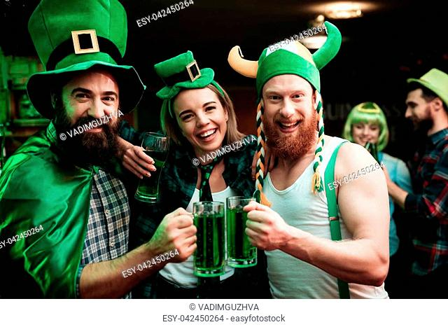 Two men and girl in carnival hats drinking beer at the bar. They celebrate St. Patrick's Day. They are having fun