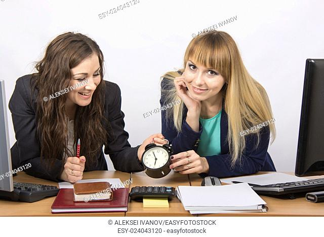 Two girls in the office happily waiting for the end of the working day