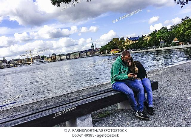Stockholm, Sweden A couple sit on a bench on the island of Kastellholmen