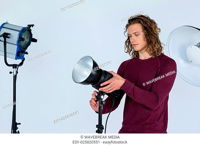 Photographer fixing spotlight