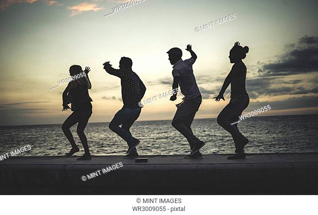 Four people dancing in a line on a sea wall in front of the ocean