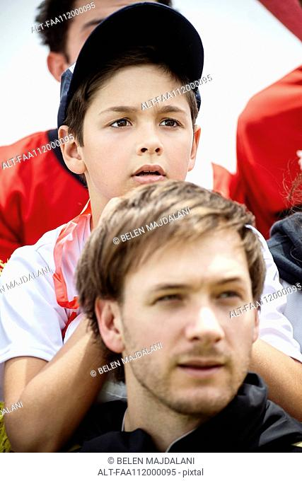 Father and son watching football match together