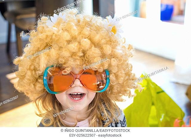 funny portrait of three years old child disguised as sixties, with great curly blond hair wig with daisy flowers on head, with orange and green colorful glasses
