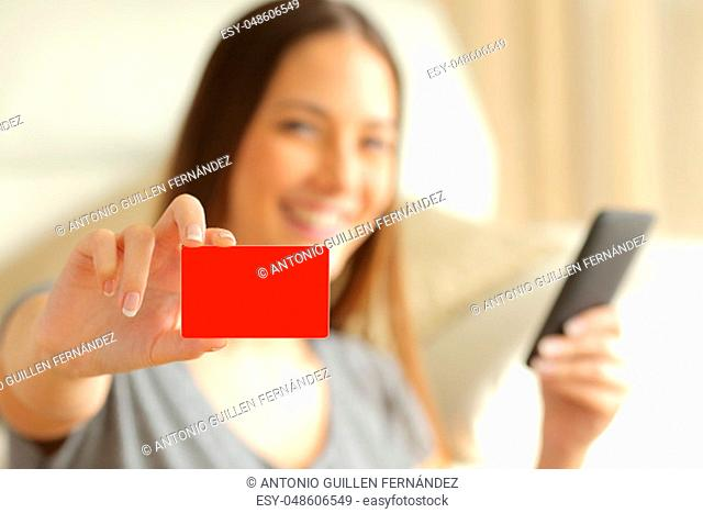 On line buyer holding a smart phone is showing a blank credit card and looking at camera