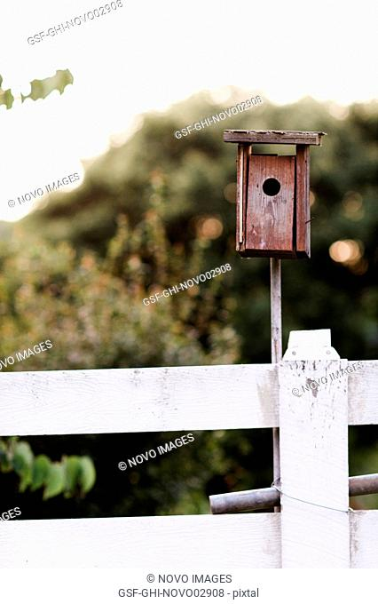 Red Birdhouse on White Fence