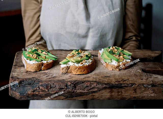 Woman holding chopping board, with ricotta, avocado and walnut bruschetta on top, mid section
