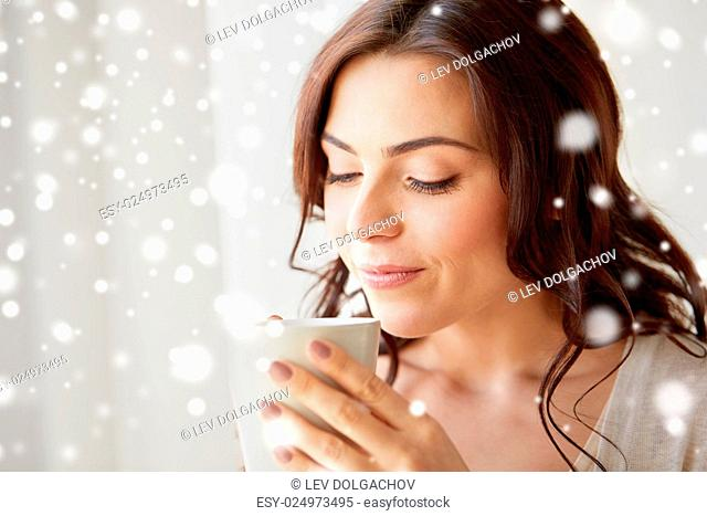 people, drinks, christmas, winter and leisure concept - close up of happy young woman with cup of tea or coffee at home over snow