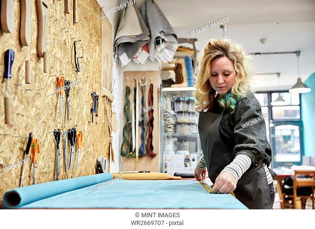 A woman preparing, measuring and cutting upholstery fabric on a workbench