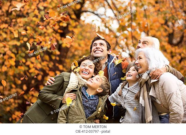 Family playing in autumn leaves in park
