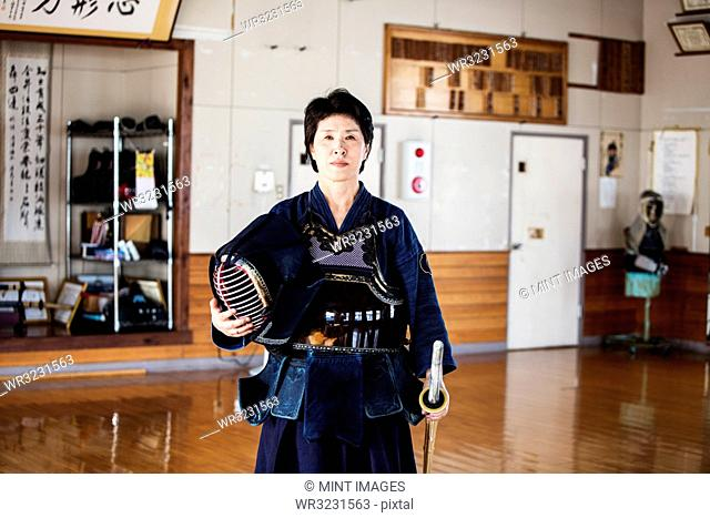 Female Japanese Kendo fighter standing in a gym, holding Kendo mask and sword, looking at camera