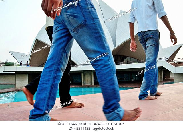 Indian visitors walking barefoot in front of Lotus Temple, India