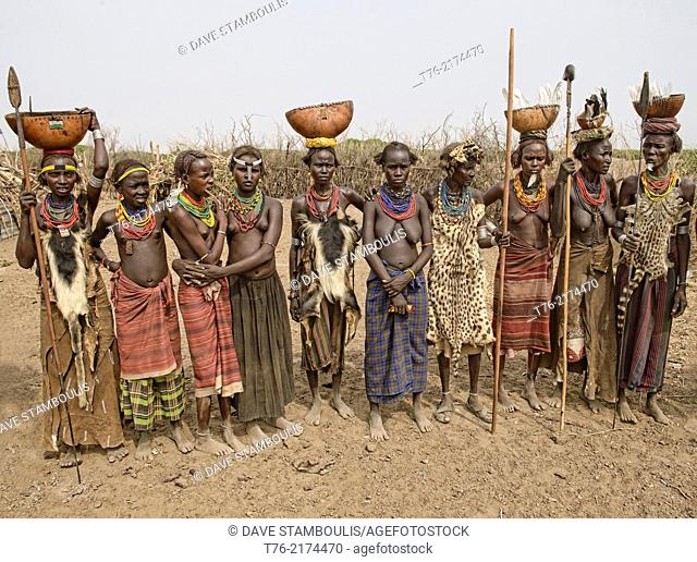 Dassanech women with hyena pelt skins and jugs on their heads in the Lower Omo Valley of Ethiopia