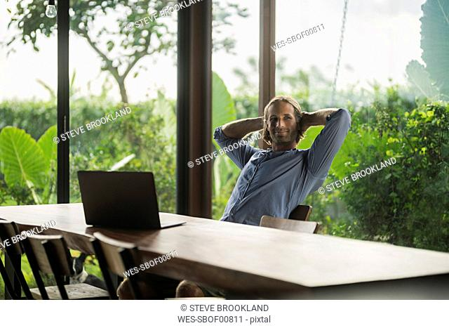 Handsome man with laptop sitting at modern wooden table in contemporary design house