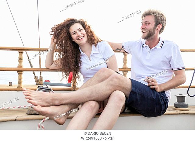 Young couple relaxing on sailboat