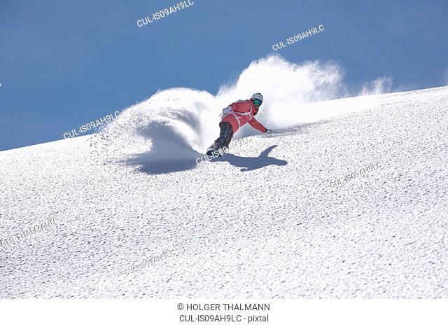 Young woman snowboarding on mountain, Hintertux, Tyrol, Austria