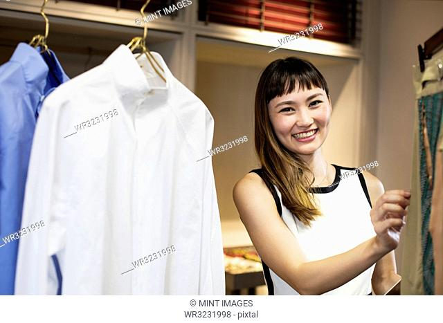 Smiling Japanese saleswoman standing in clothing store, looking at shirt