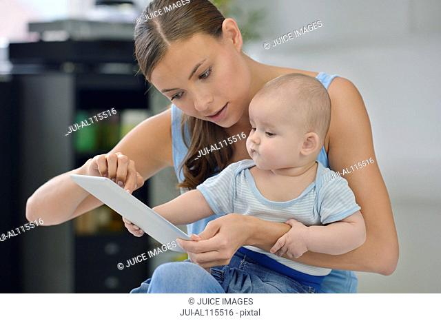 Baby boy touching digital tablet with mother
