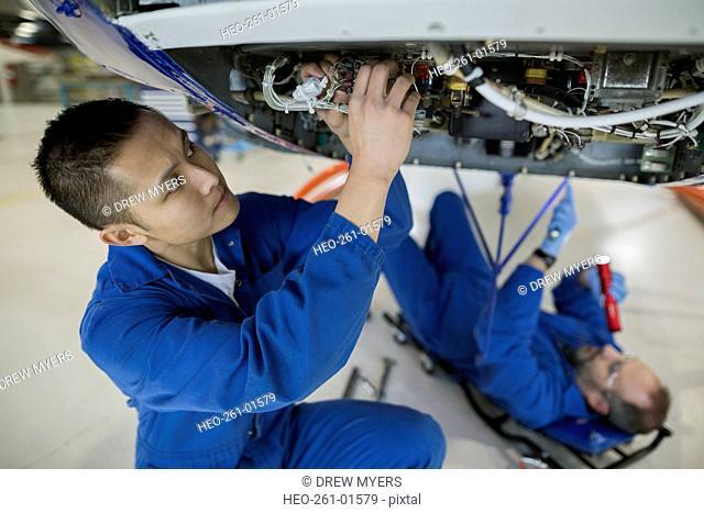 Mechanics working underneath helicopter