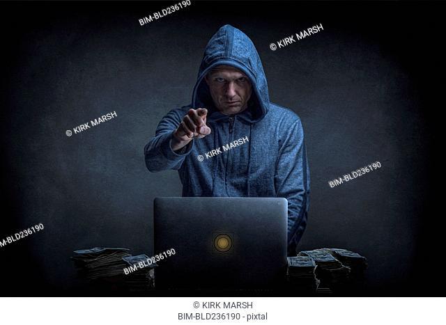 Caucasian hacker stealing money from laptop