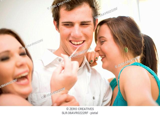 Teenage girls putting makeup on boy