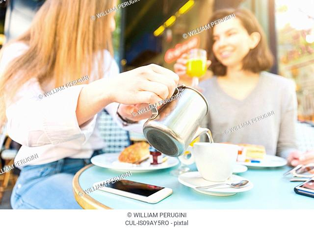 Two young women pouring breakfast coffee at sidewalk cafe, Paris, France