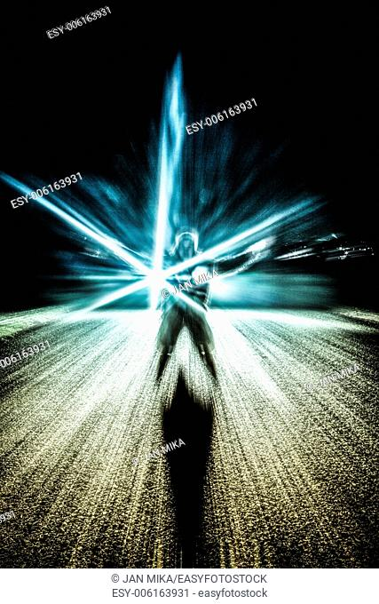 Abstract photo of a man and light effects over dark background