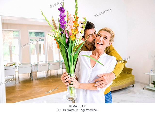 Romantic mature man kissing wife on cheek whilst gifting flowers in dining room
