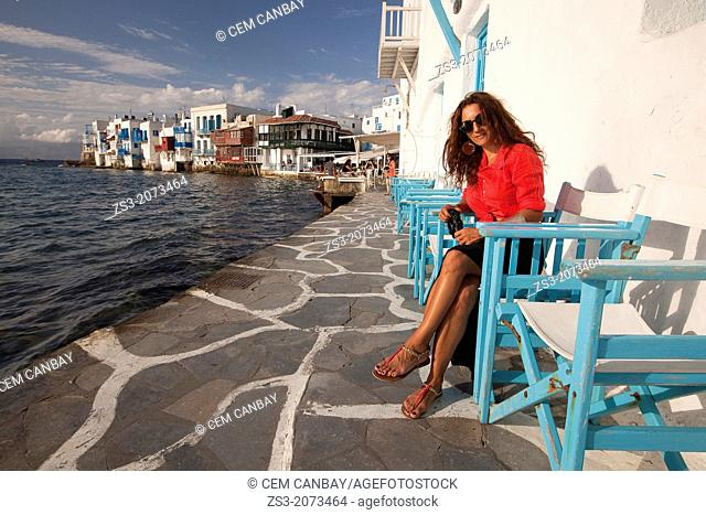 Woman with a camera posing in Little Venice district, Mykonos, Cyclades Islands, Greek Islands, Greece, Europe