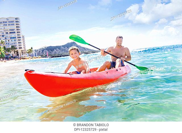 A father and son spending time kayaking together off of Waikiki beach,; Honolulu, Oahu, Hawaii, United States of America