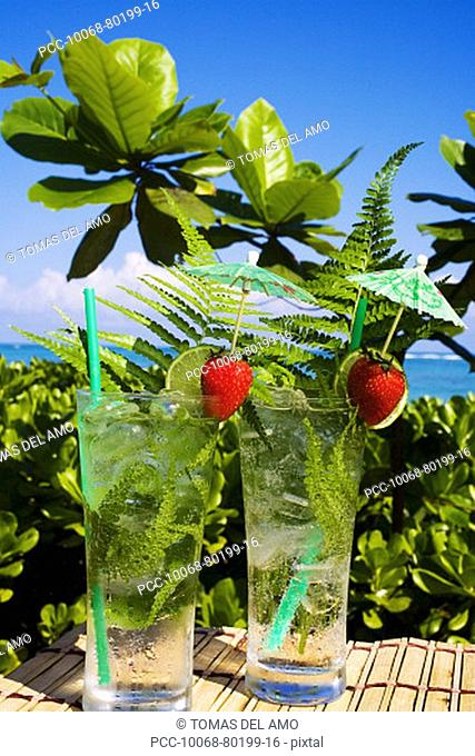 Tropical cocktails garnished with fruit and green fern leaves in outdoor setting