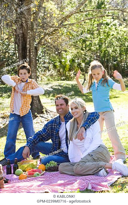 Young happy family in park, children dancing around