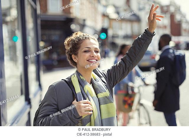 Smiling young woman hailing taxi on sunny urban street