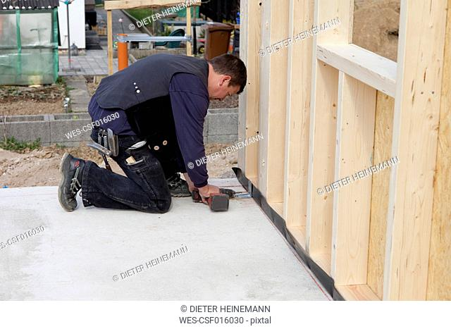 Europe, Germany, Rhineland Palatinate, Man fixing wooden wall with installing bracket