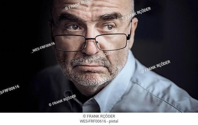 Portrait of serious looking senior man wearing glasses