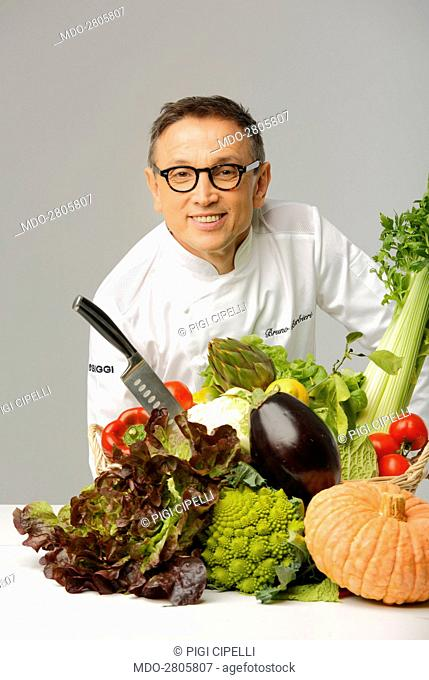 The chef and judge of the talent show MasterChef Italia Bruno Barbieri leaning on a counter covered with vegetables for a photo shooting