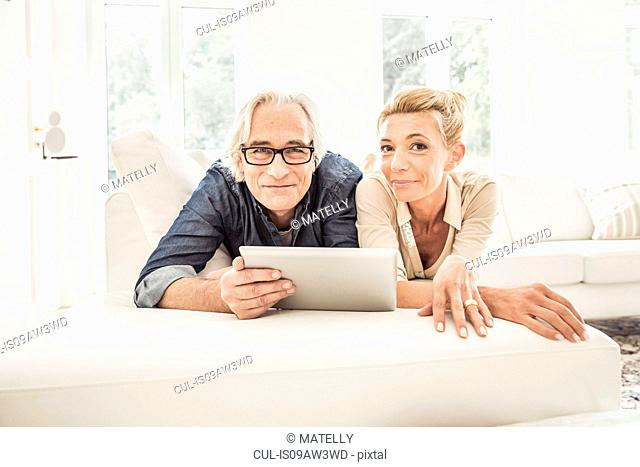 Couple relaxing on sofa, looking at digital tablet